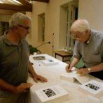 Nella foto: don Mario Pini a Marola mentre firma le copie del libro; con lui, il diacono  permanente Carlo Prati